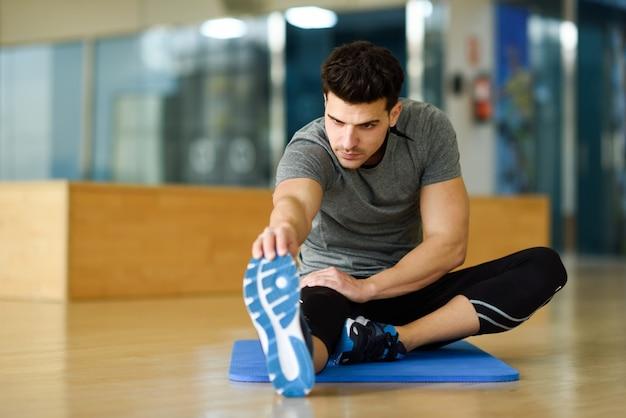 Młody człowiek rozciąga nogi w siłowni.