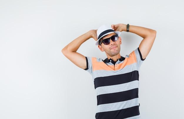Młody człowiek, rozciągając ramiona w t-shirt i czapkę i wyglądający na zrelaksowanego