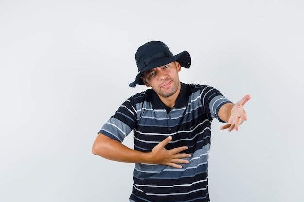Młody człowiek rozciągający rękę o pomoc w t-shirt, kapelusz i patrząc nieszczęśliwy, widok z przodu.
