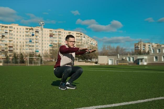 Młody człowiek rozciągający się na stadionie w okularach