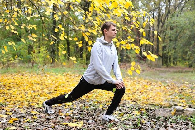 Młody człowiek rozgrzewa się i rozciąga nogi przed porannym treningiem w parku jesień