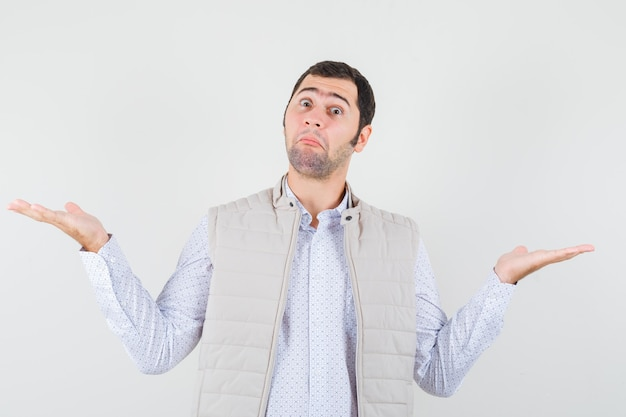 Młody człowiek rozkładający dłonie w pytający sposób w beżowej kurtce i patrząc zamyślony, widok z przodu.
