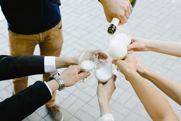 Młody człowiek rozlewa szampana w okularach swoich przyjaciół