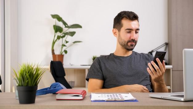 Młody człowiek rozmawia przez telefon, gdy jest w biurze. mądry człowiek dbający o biznes.
