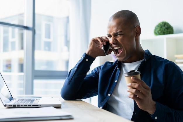 Młody człowiek rozmawia przez telefon komórkowy w biurze. afrykański dyrektor siedzący przy biurku z laptopem