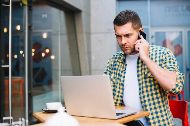 Młody człowiek rozmawia przez telefon poważnie