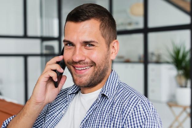 Młody człowiek rozmawia przez telefon, siedząc na kanapie