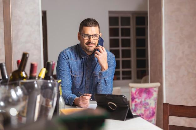 Młody człowiek rozmawia przez telefon w okularach i koszuli