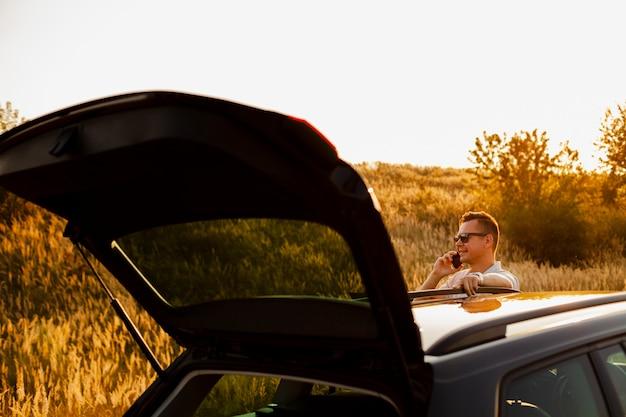 Młody człowiek rozmawia przez telefon w pobliżu samochodu