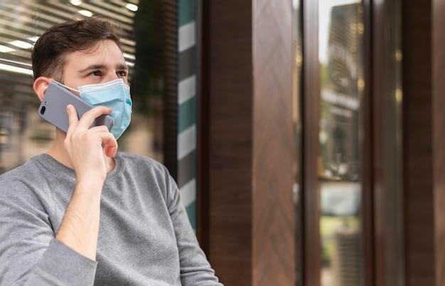 Młody człowiek rozmawia przez telefon z maską medyczną