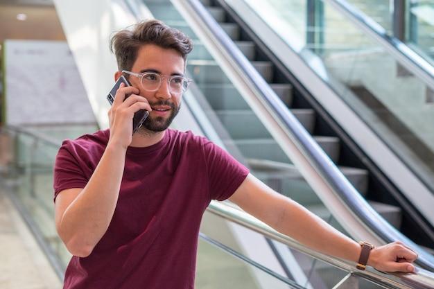 Młody człowiek rozmawia telefon komórkowy na lotnisku