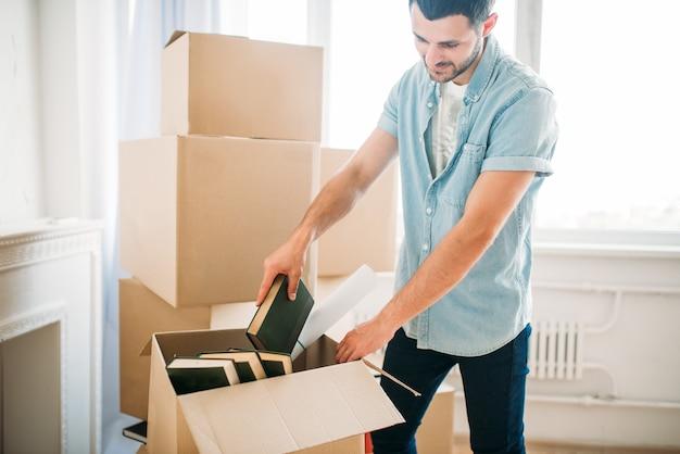 Młody człowiek rozpakowuje kartony z książkami, parapetówkę. przeprowadzka do nowego domu