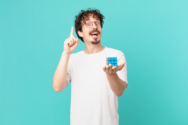 Młody człowiek rozwiązujący problem z inteligencją, czujący się jak szczęśliwy i podekscytowany geniusz po zrealizowaniu pomysłu