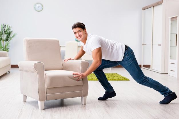 Młody człowiek ruchomych mebli w domu