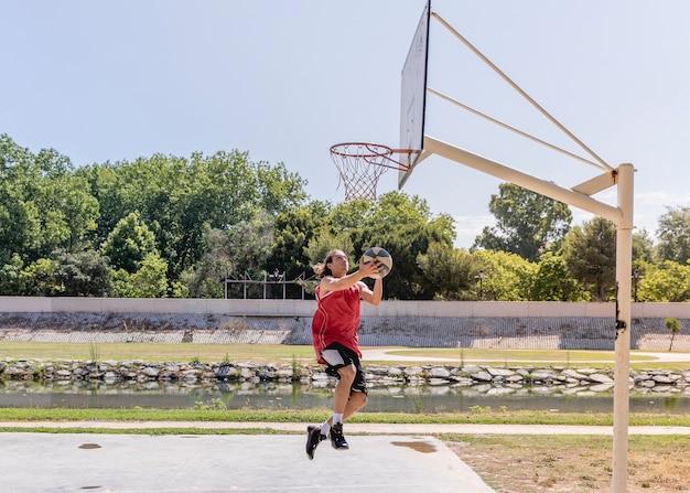 Młody człowiek rzuca koszykówkę w obręcz