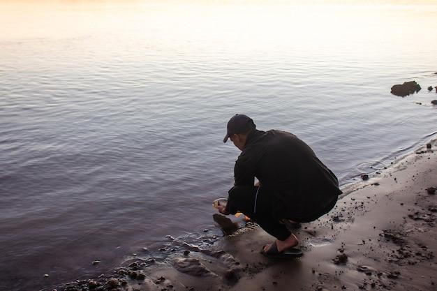Młody człowiek rzuca ryby z powrotem do wody na brzegu rzeki.