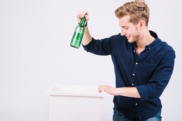 Młody człowiek rzuca zielone butelki w śmietniku