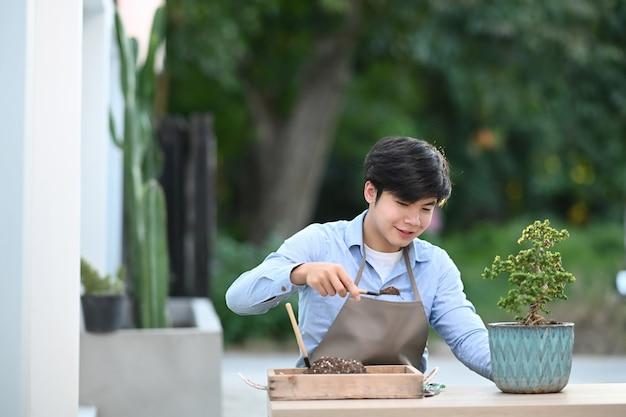 Młody człowiek sadzący drzewko bonsai do doniczki w domu.