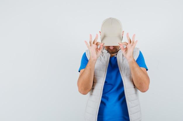 Młody człowiek ściągający czapkę na oczy w t-shircie, kurtce i wyglądający fajnie, widok z przodu.