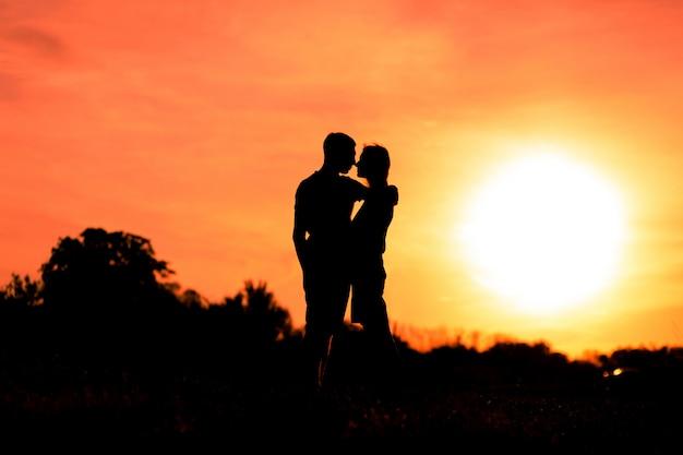 Młody człowiek ściska jego dziewczyny na zmierzchu niebie