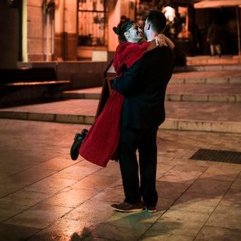 Młody człowiek ściska wiszącej roześmianej kobiety na ulicie w wieczór