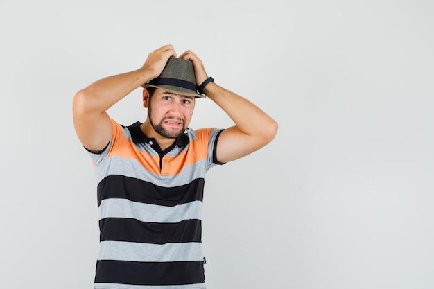 Młody człowiek, ściskając głowę w dłonie w t-shirt, kapelusz i patrząc niespokojnie, widok z przodu.