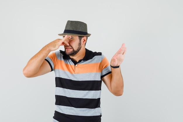 Młody człowiek ściskający nos z powodu nieprzyjemnego zapachu w koszulce, kapeluszu i wyglądający na zniesmaczonego, widok z przodu.
