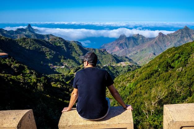 Młody człowiek siedzący patrząc na góry anaga na północy teneryfy w hiszpanii