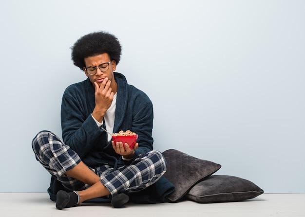 Młody człowiek siedzi i je śniadanie