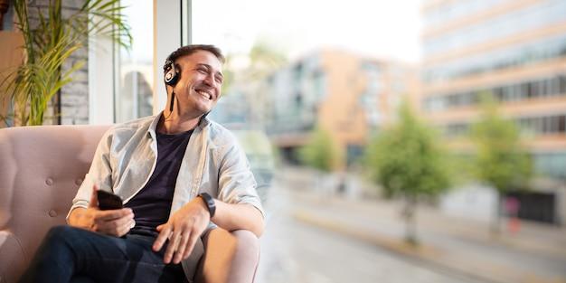 Młody człowiek siedzi i mówi bez użycia rąk i uśmiecha się