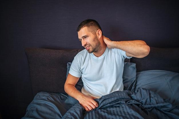 Młody człowiek siedzi na łóżku i odczuwa ból w okolicy szyi. kurczy się i patrzy w lewo. facet trzyma rękę za szyją. jest częściowo przykryty kocem.