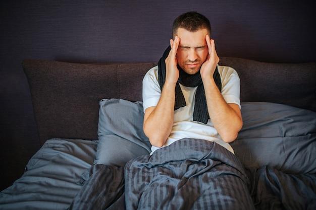 Młody człowiek siedzi na łóżku i trzyma ręce blisko czoła. boli go głowa. ból jest silny i okropny. facet się kurczy. ma szalik na szyi.