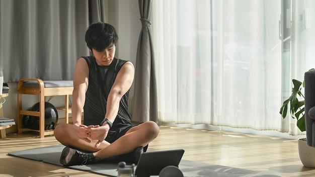 Młody człowiek siedzi na macie do jogi i rozciągając ramiona.