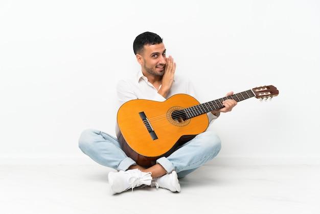 Młody człowiek siedzi na podłodze z gitarą szepcząc coś