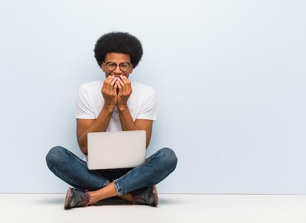 Młody człowiek siedzi na podłodze z laptopem, śmiejąc się z czegoś, zakrywając usta rękami