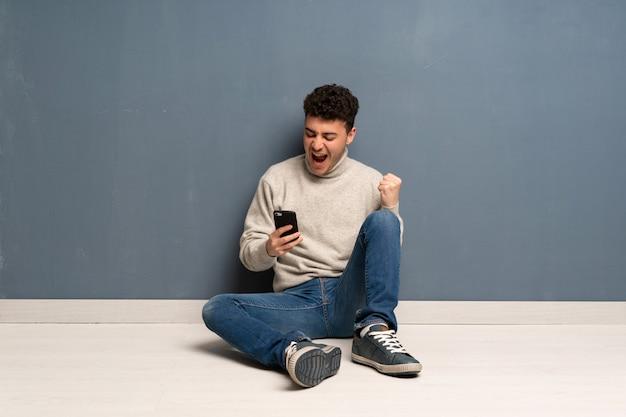 Młody człowiek siedzi na podłodze z telefonem w pozycji zwycięstwa
