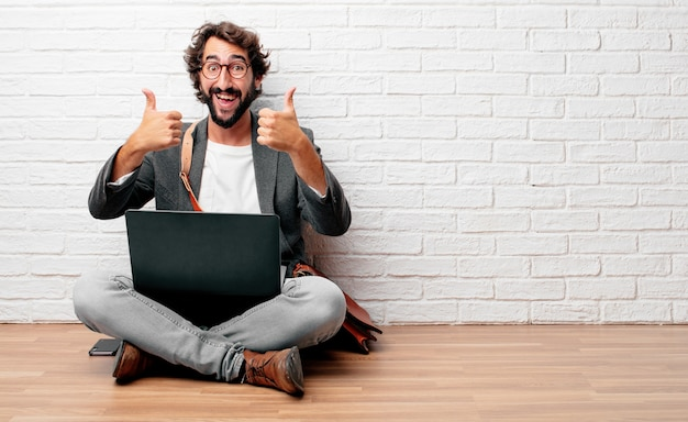 Młody człowiek siedzi na podłodze z zadowolony, dumny i szczęśliwy wygląd z kciuki do góry