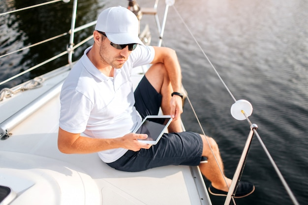 Młody człowiek siedzi na skraju jachtu i przytrzymaj tablet. mężczyzna nosi okulary przeciwsłoneczne i białą czapkę z koszulą. on jest poważny i pewny siebie. sailor odpocznij.