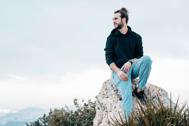 Młody człowiek siedzi na szczycie skały, patrząc na widok