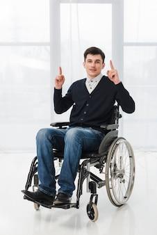 Młody człowiek siedzi na wózku inwalidzkim, pokazując jego palec w górę patrząc na kamery
