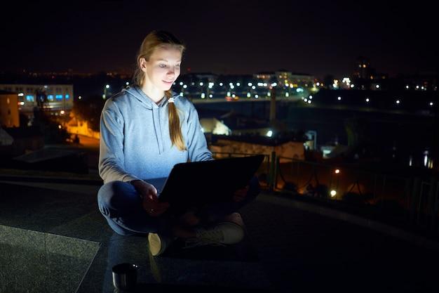 Młody człowiek siedzi na zewnątrz i pracuje z laptopem w nocy,