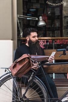 Młody człowiek siedzi na zewnątrz kawiarni na ławce z rowerem za pomocą telefonu komórkowego
