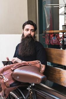 Młody człowiek siedzi na zewnątrz kawiarni z jego rower
