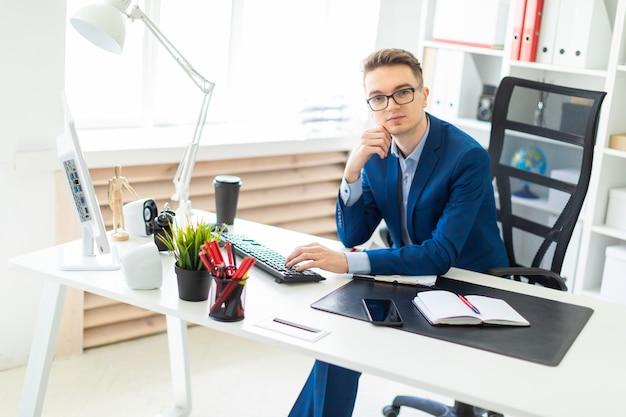 Młody człowiek siedzi przy biurku w biurze i pracy na komputerze.