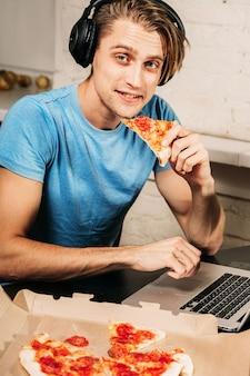 Młody człowiek siedzi przy komputerze z pizzą w domu.