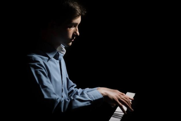 Młody człowiek siedzi przy pianinie.