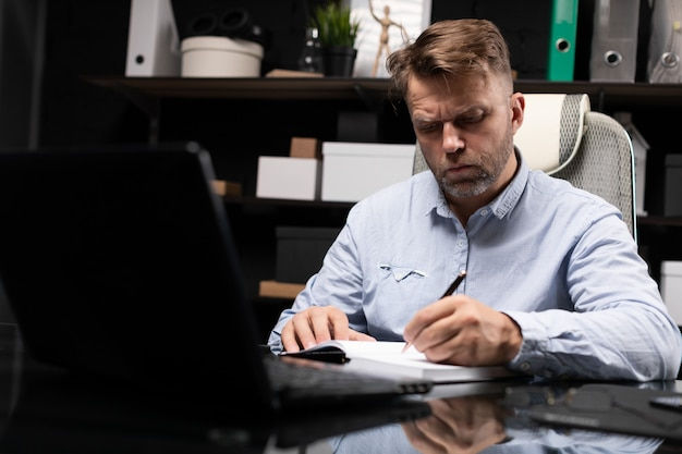 Młody człowiek siedzi przy stole komputera i robi notatki w pamiętniku