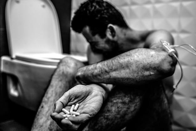 Młody człowiek siedzi samotnie na podłodze w toalecie i bierze narkotyki. pokazuje garść pigułek na złe dyktowanie. facet cierpi i płacze. ręka owinięta warkoczem narkotykowym. czarno-biały obraz. bezbarwny