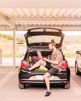 Młody człowiek siedzi w bagażniku z laptopem