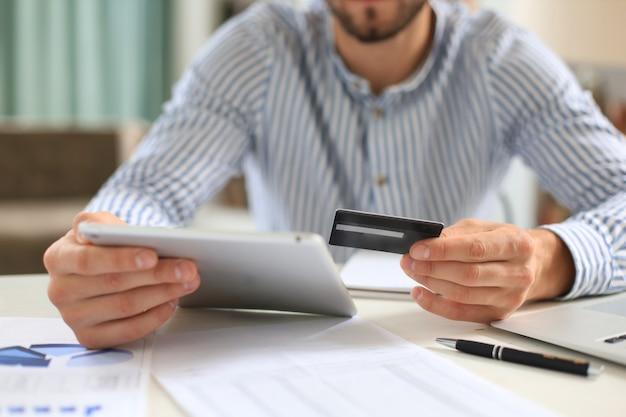 Młody człowiek siedzi w biurze i płaci kartą kredytową ze swoim tabletem.